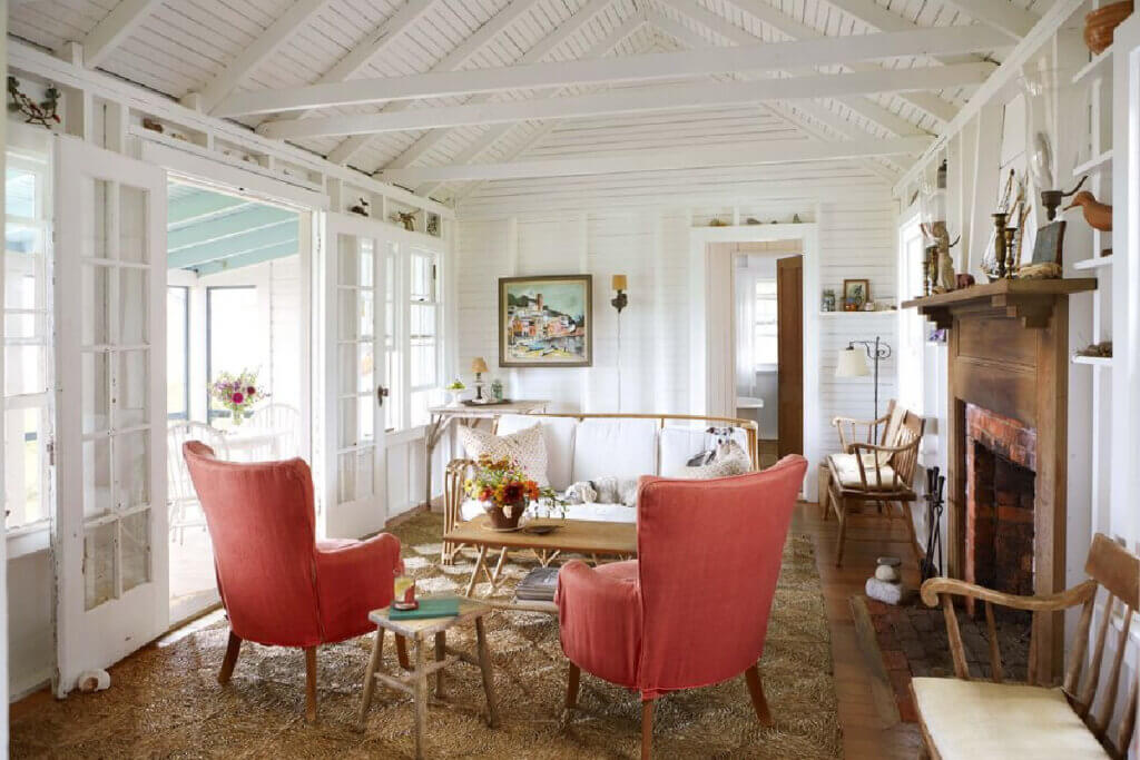 Twin wingback chairs across from a rattan sofa are in the front room of the beach cottage