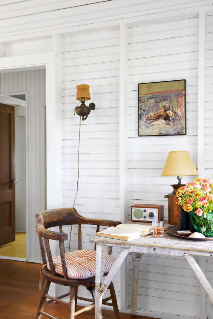 An old chair adds seating to the old wicker table in the Martha's Vineyard beach cottage.