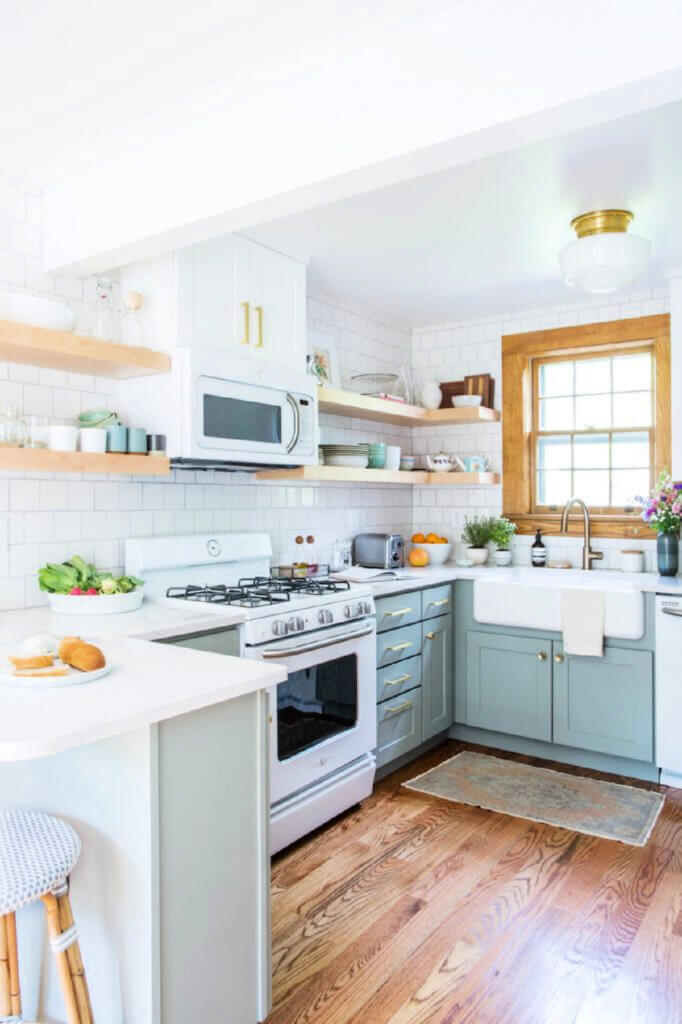 The kitchen with light blue cabinets and white countertops in this Tennessee Tudor home