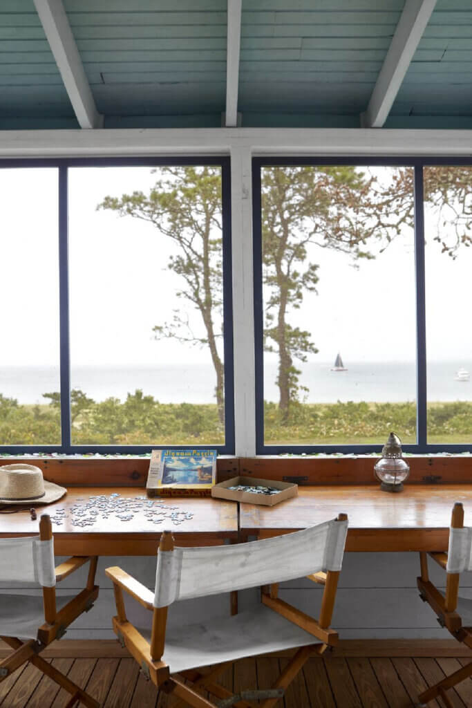 Director chairs in front of a table against the wall are where the family gather to put jigsaw puzzles together. The view is of the water.