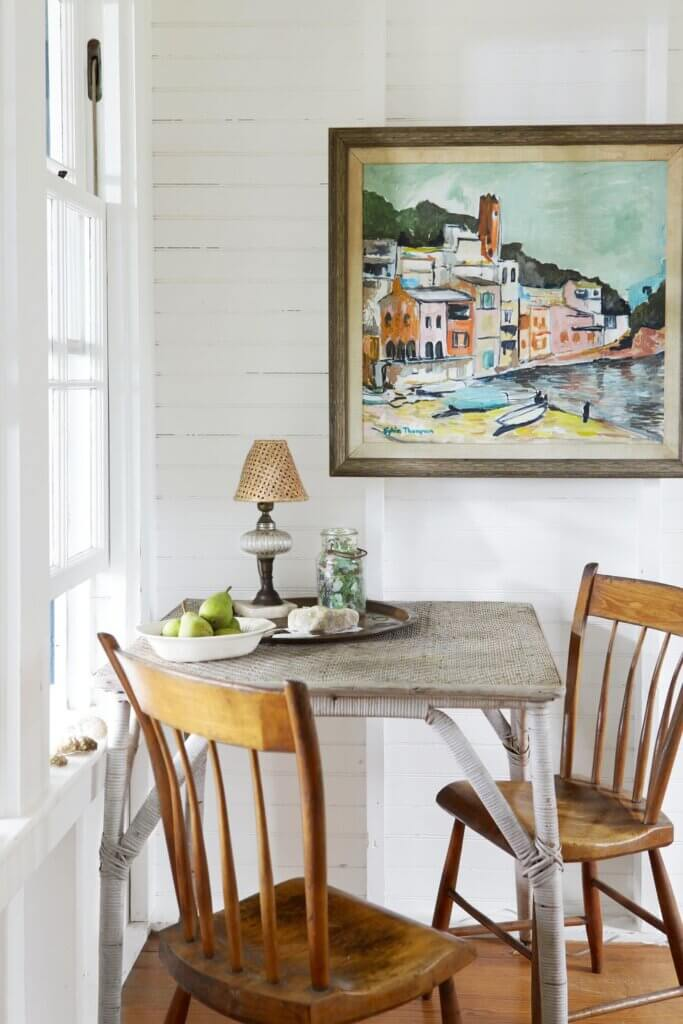 Two wood chairs and a weathered wicker table is a perfect place for a game of cards at this Martha's Vineyard beach cottage.