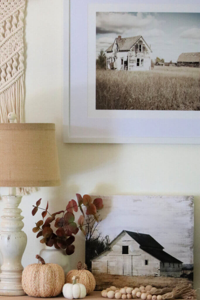 My fall living room vignette with a barn painting, a neutral lamp, faux pumpkins, a vase with faux eucalyptus leaves, and  a strand of boho beads.
