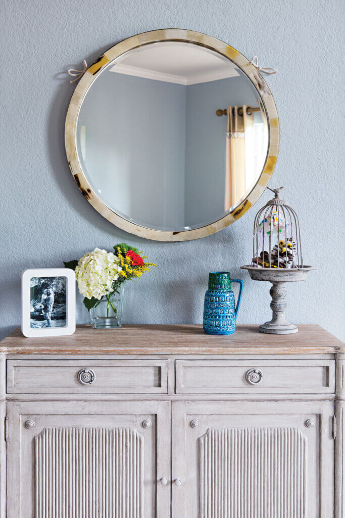 A round mirror hangs over a distressed cupboard