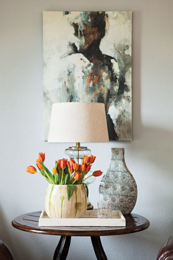 Tulips fill a vase  next to a clear lamp base and a boho container