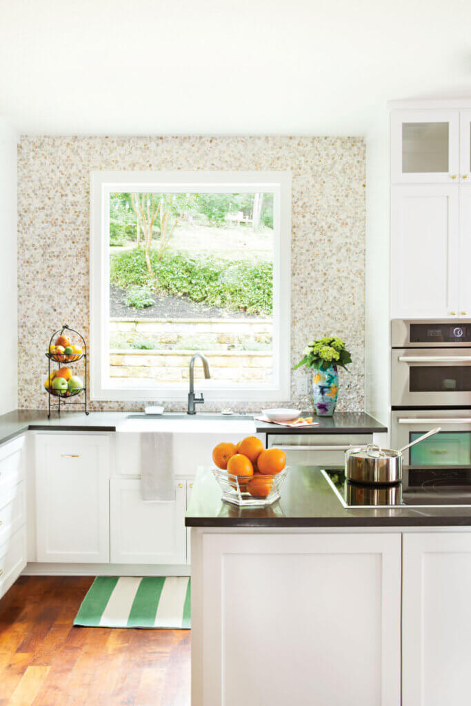 The kitchen is white with black counter tops and now feels light and airy.