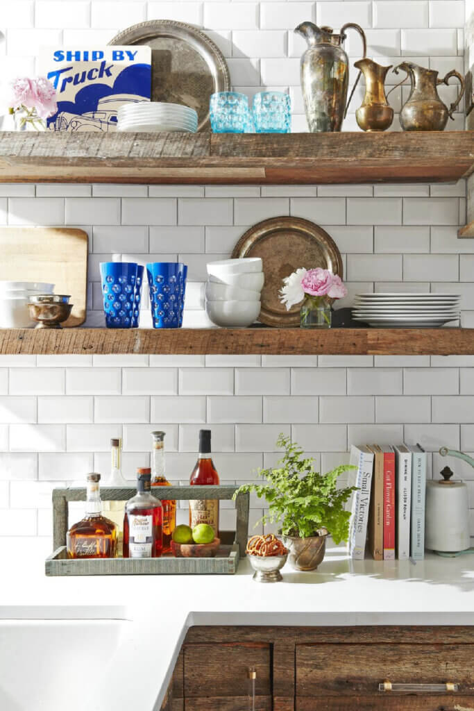 Wood shelves in the kitchen area with white subway tile.