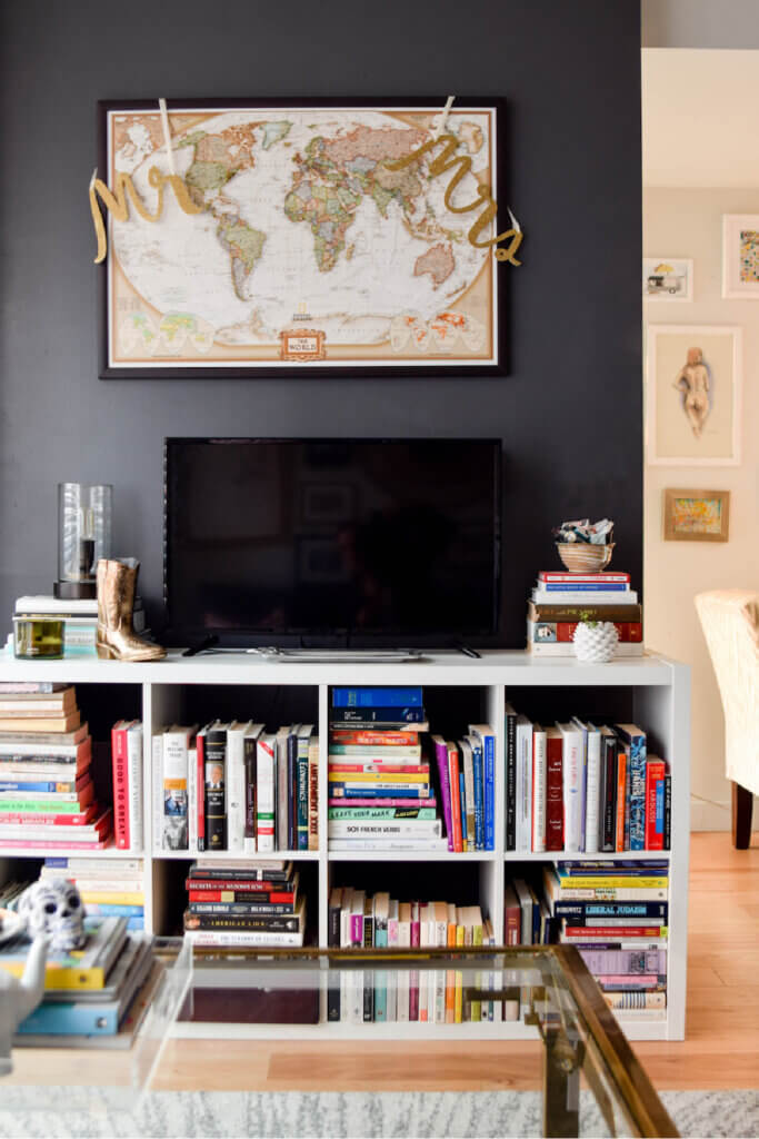 A white cubby shelf with books is the perfect place for Heather's TV in her stylish Washington DC apartment