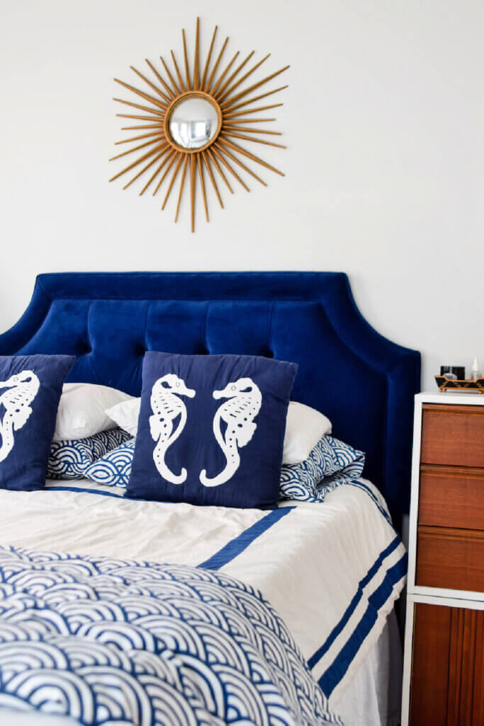 Cobalt blue and white bedding stands out against the white bedroom walls.