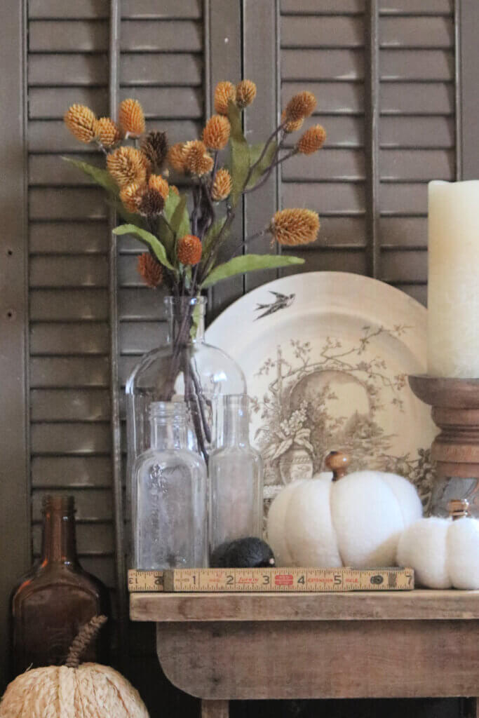 A bit of fall on a small table with vintage and neutral decor