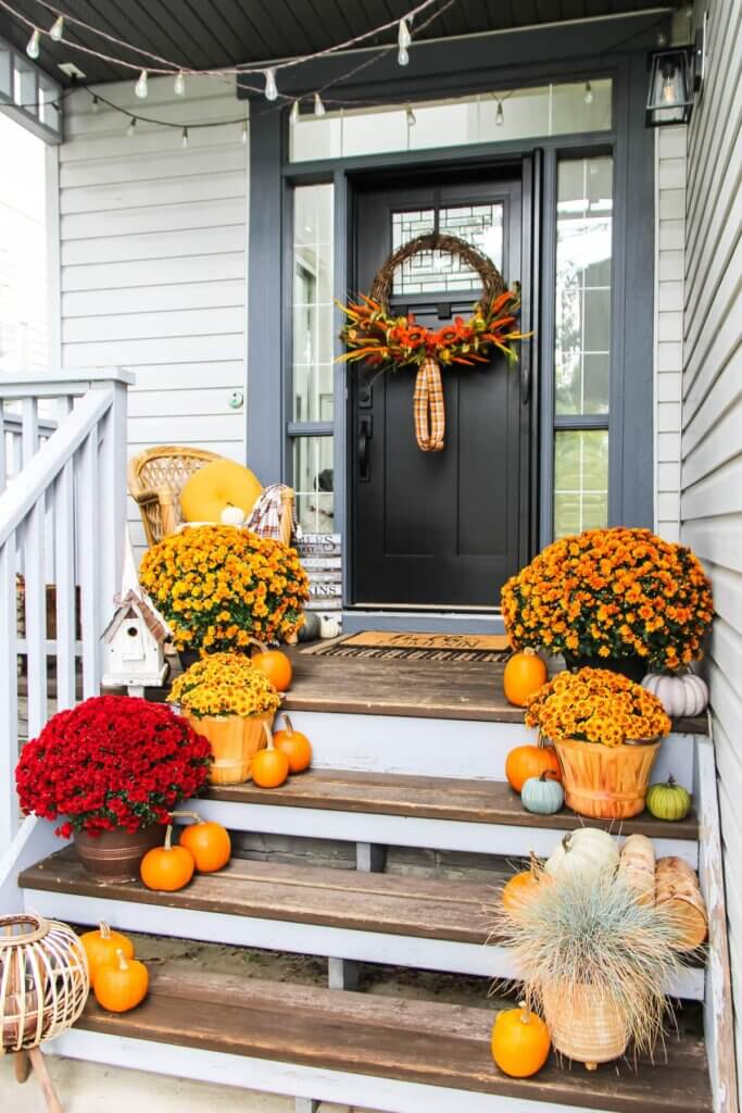 Porch fall decor with mums and pumpkins on the steps
