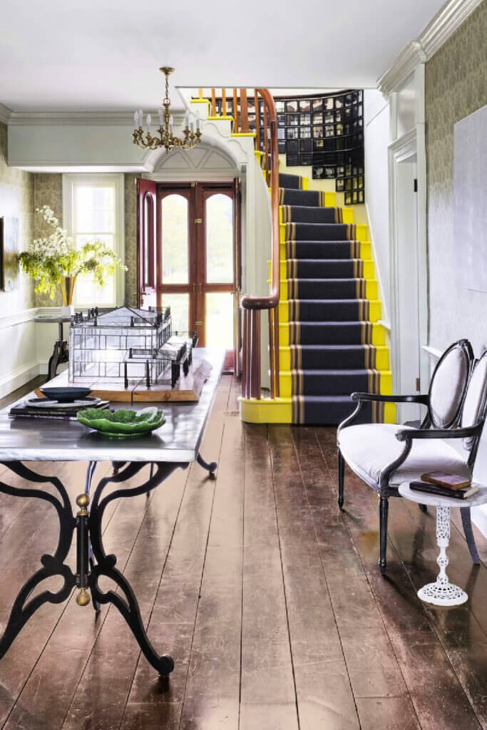 The entryway and yellow and black stairway.