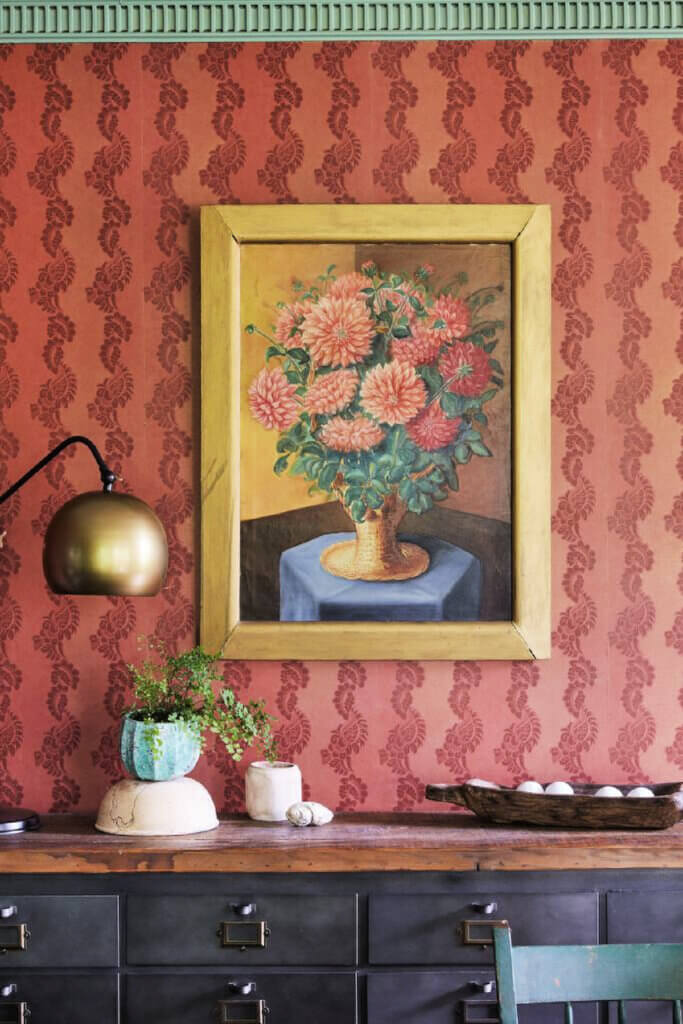 The color of the wallpaper on the walls blend well with the floral painting hung there