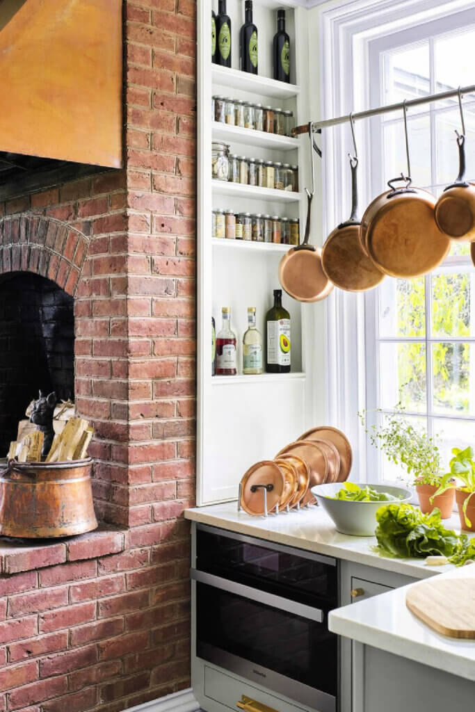 The vintage and modern New York farmhouse has a brick fireplace in the kitchen.