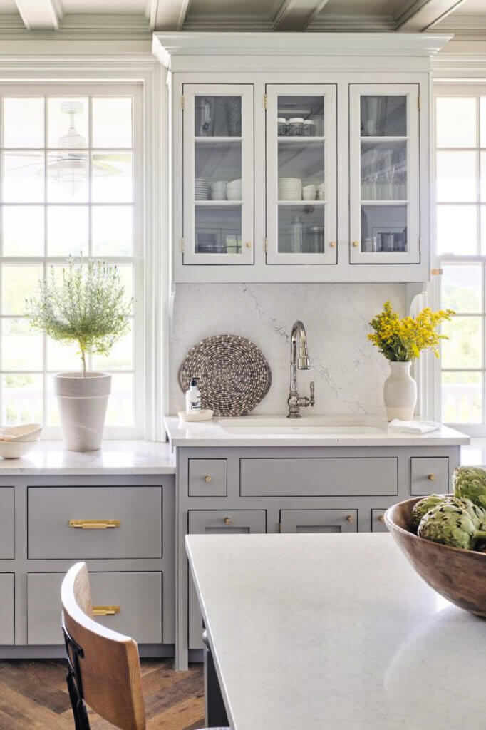 The kitchen is gray and white with gold hardware